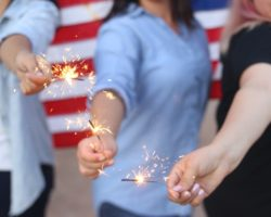 Weman holding sparklers with american flag background