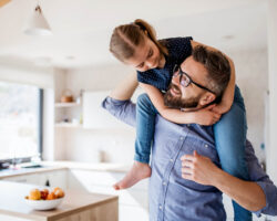 smiling happy dad holding his daughter on his shoulders in kitchen