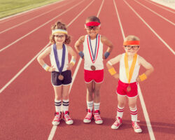 three children standing on a track field with medals from competitions