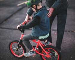 Man helps hold and steady his son as he learns to ride a bike.